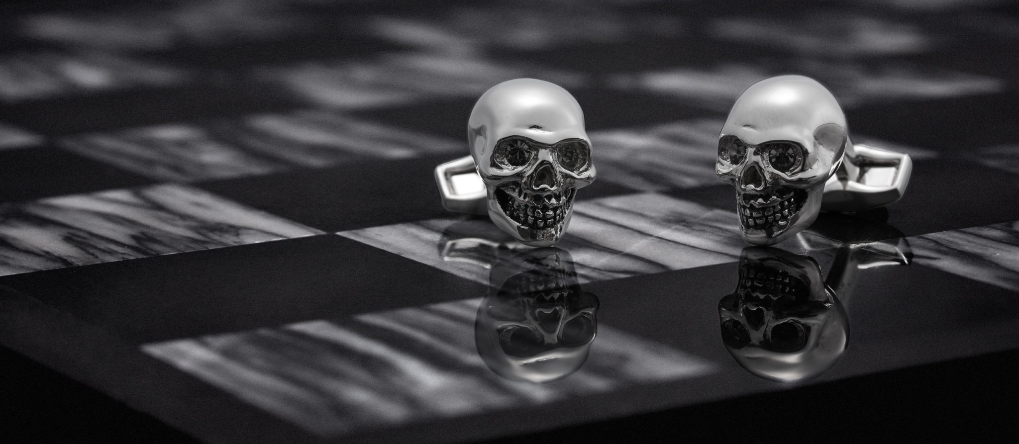 dark and moody marketing photograph of Alexander Mcqueen skull cufflinks on a black and white marble chess board
