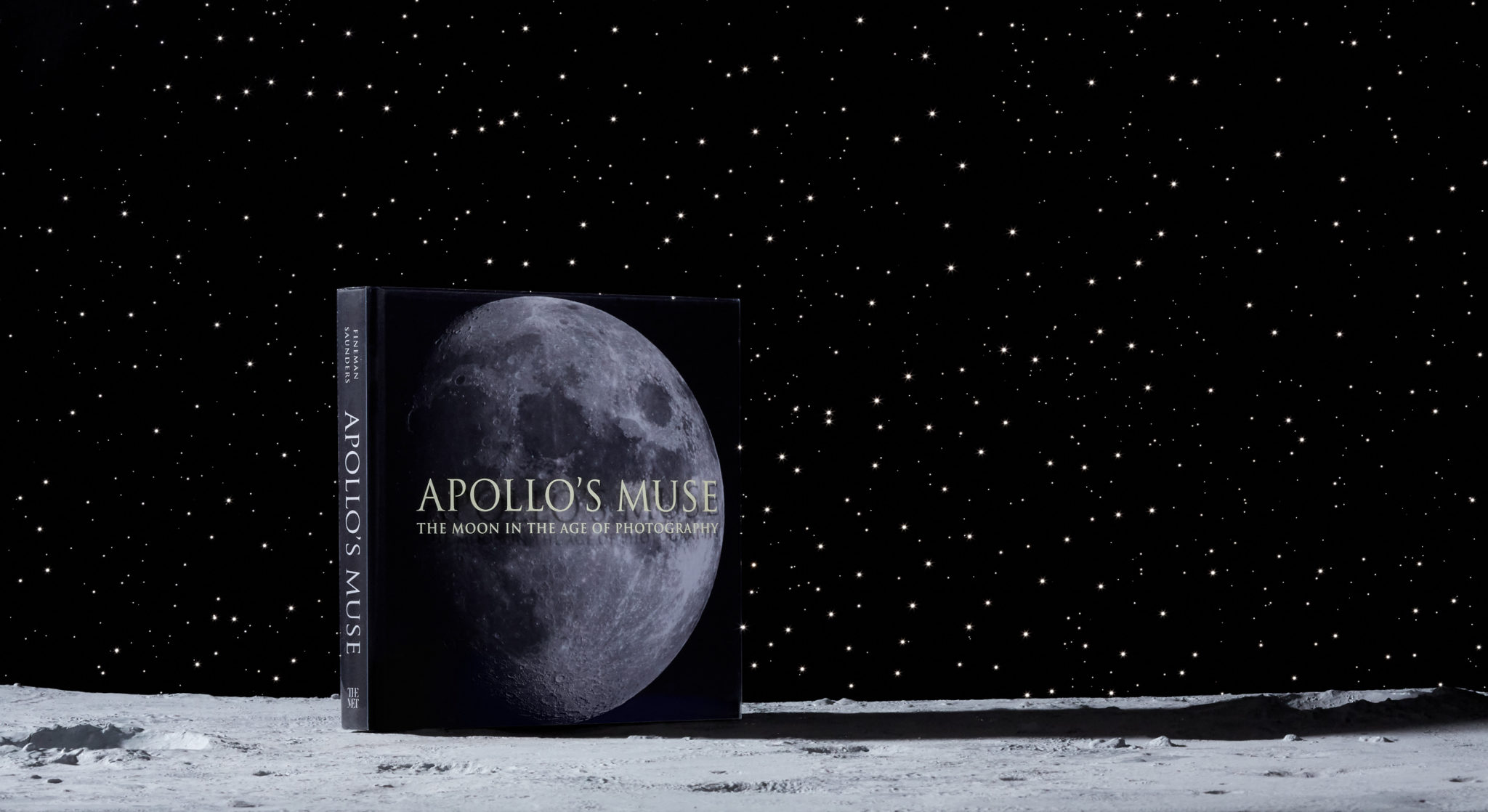 marketing still life photograph of the Apollo's Muse exhibition catalog book on the moon with a star-field background