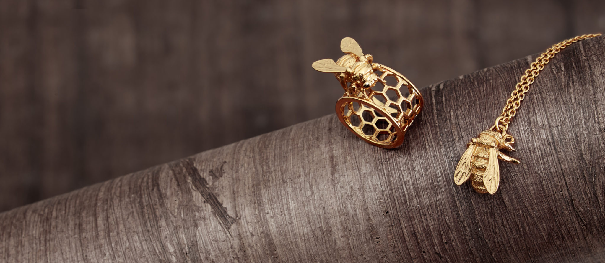gold bee ring and gold bee necklace on wood branch