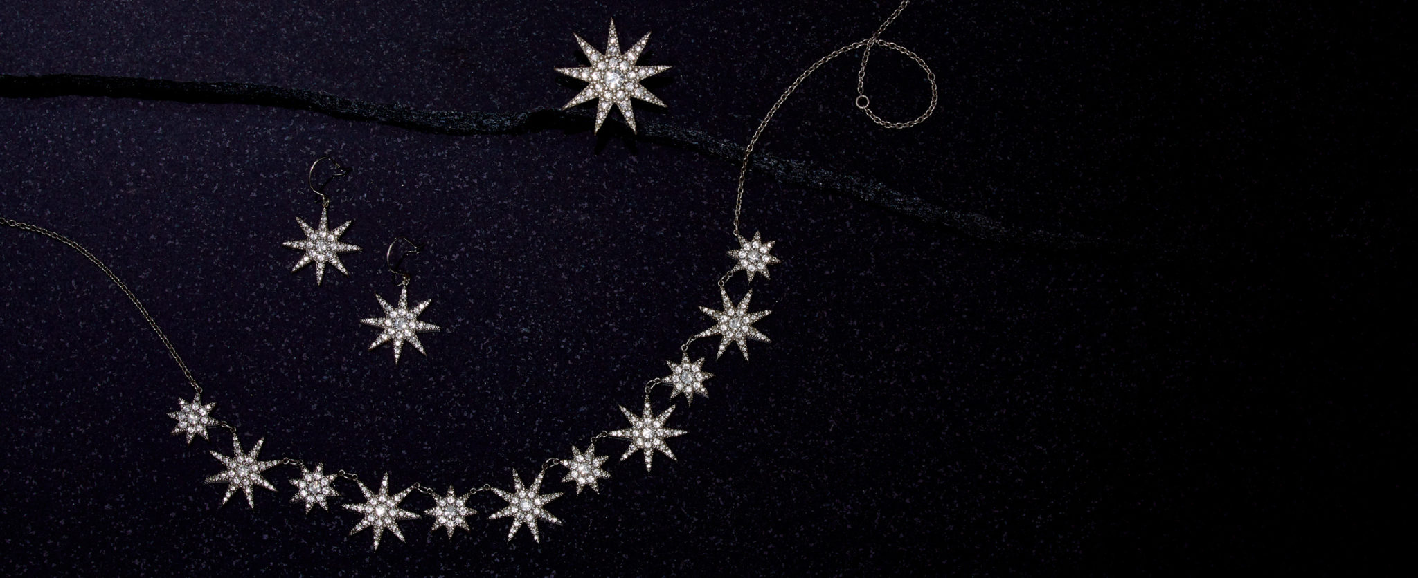 group jewelry photograph of a silver and pave diamond necklace, earrings, and pin all in the shape of an Ottoman star on dark dark purple speckled granite evoking the night sky