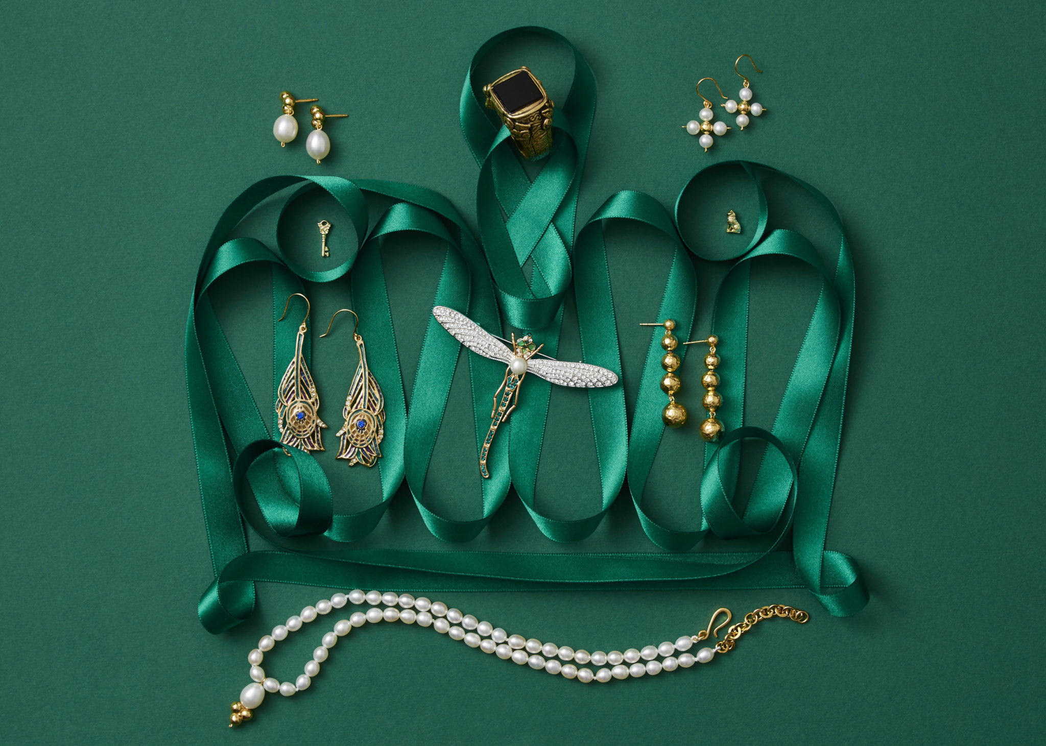 marketing still life photograph of a crown made of green ribbon adorned with gold and pearl jewelry including earrings, a pin, a ring, and a necklace on a green background.