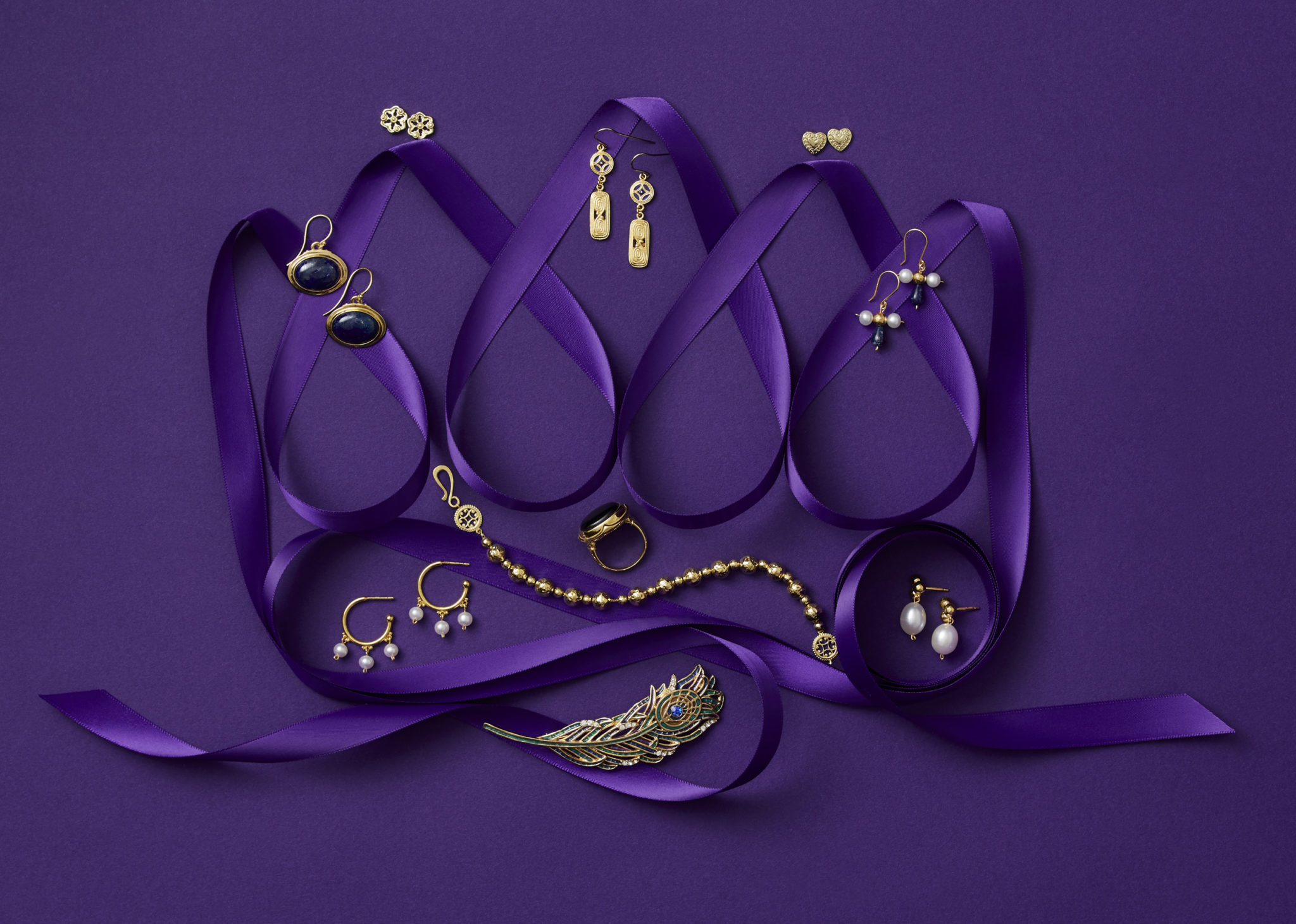 marketing still life photograph of a crown made of purple ribbon adorned with gold and pearl jewelry including earrings, a pin, a ring, and bracelets on a purple background.