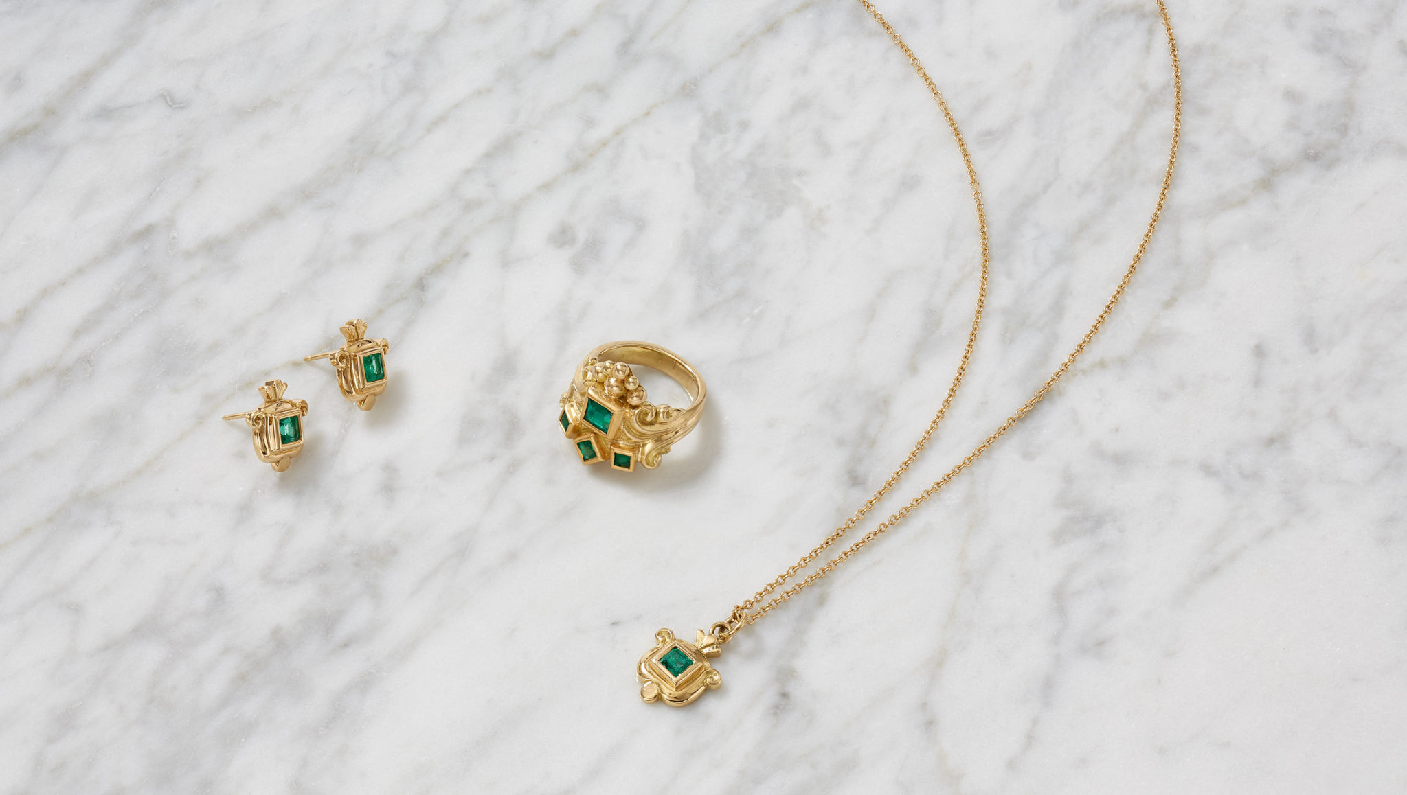 marketing still life photograph of gold and emerald jewelry on a marble background