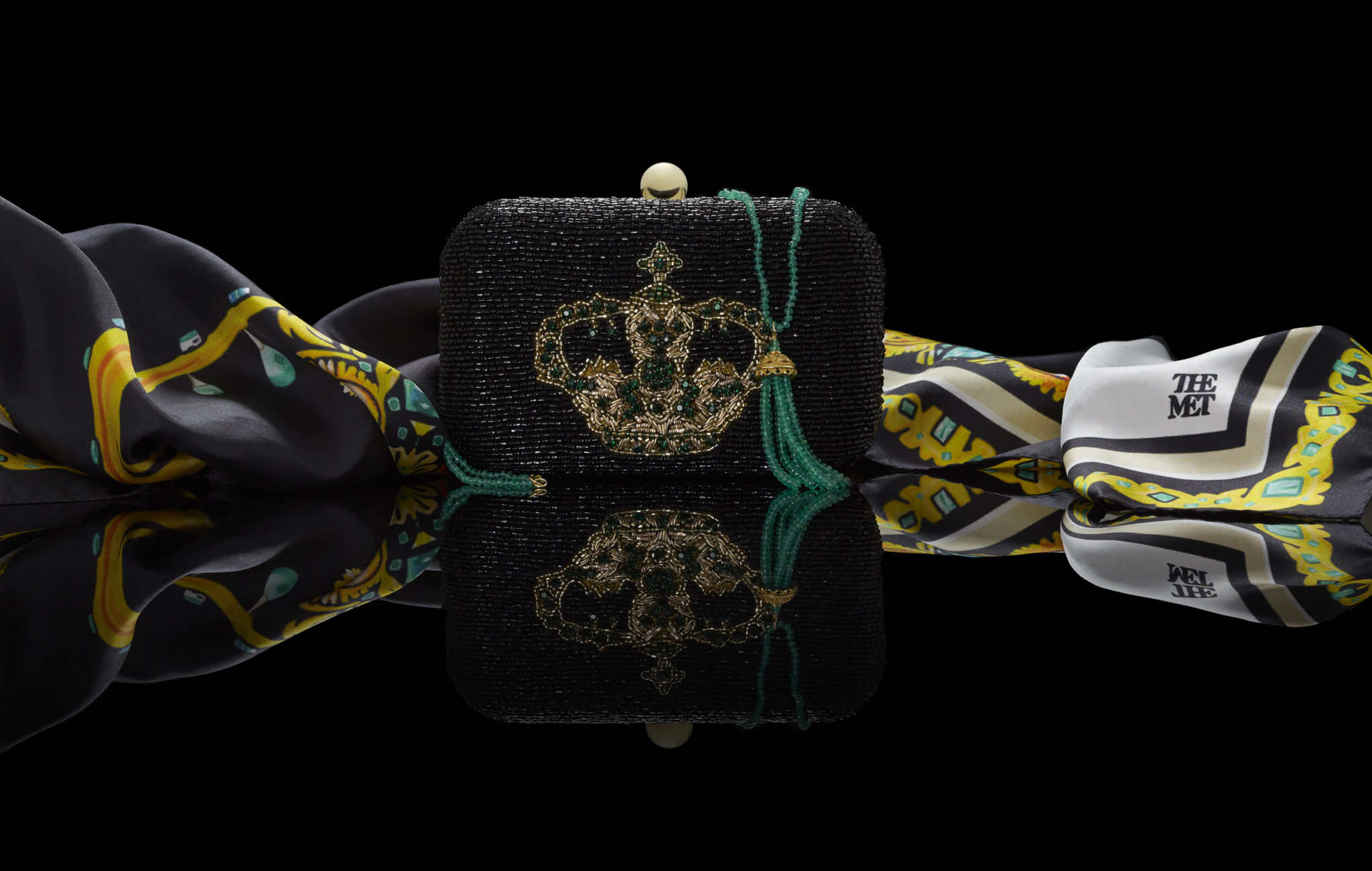 marketing still life photograph of the crown of the andes silk scarf, beaded clutch, and emerald necklace with reflection on a black background