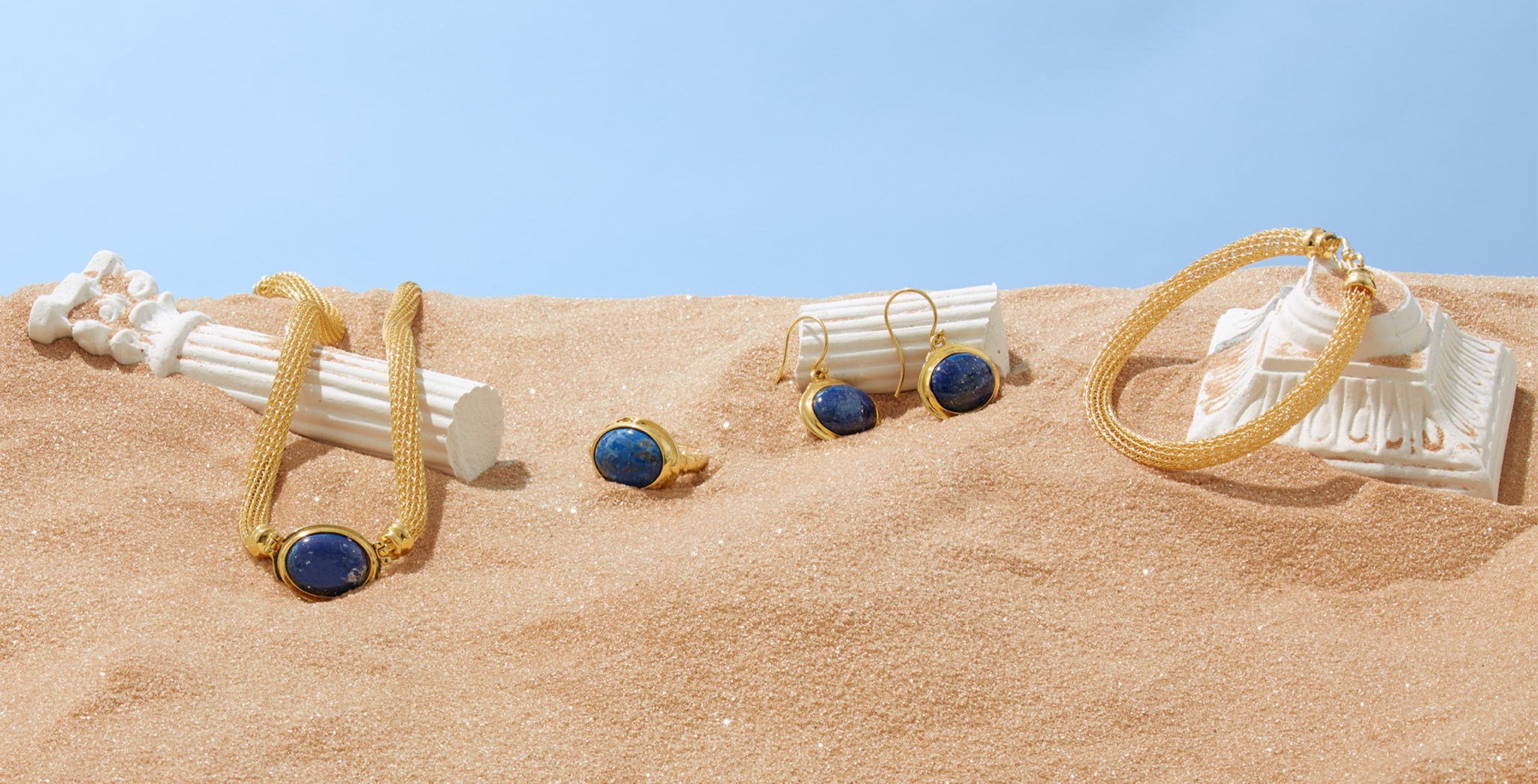 marketing still life photograph of gold and lapis cabochon jewelry draped on ruins of marble columns in the desert