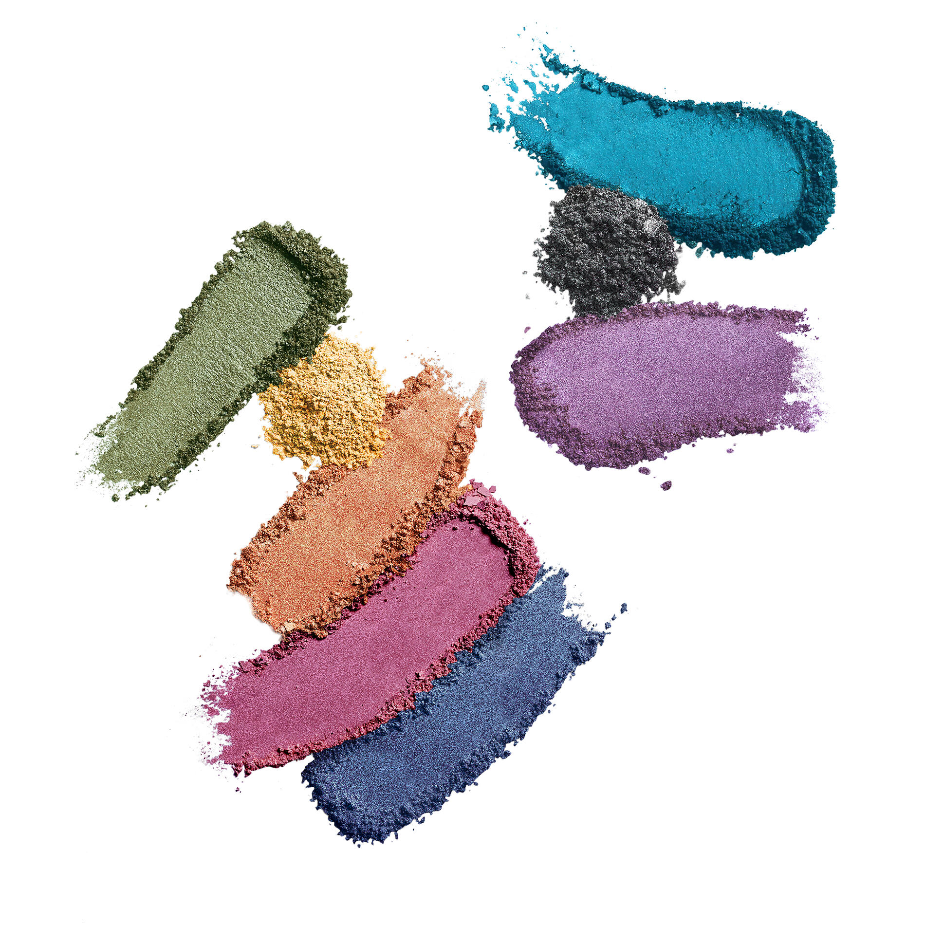 A group of colorful eyeshadows, some in little piles of powder, some smeared showing the texture of the product
