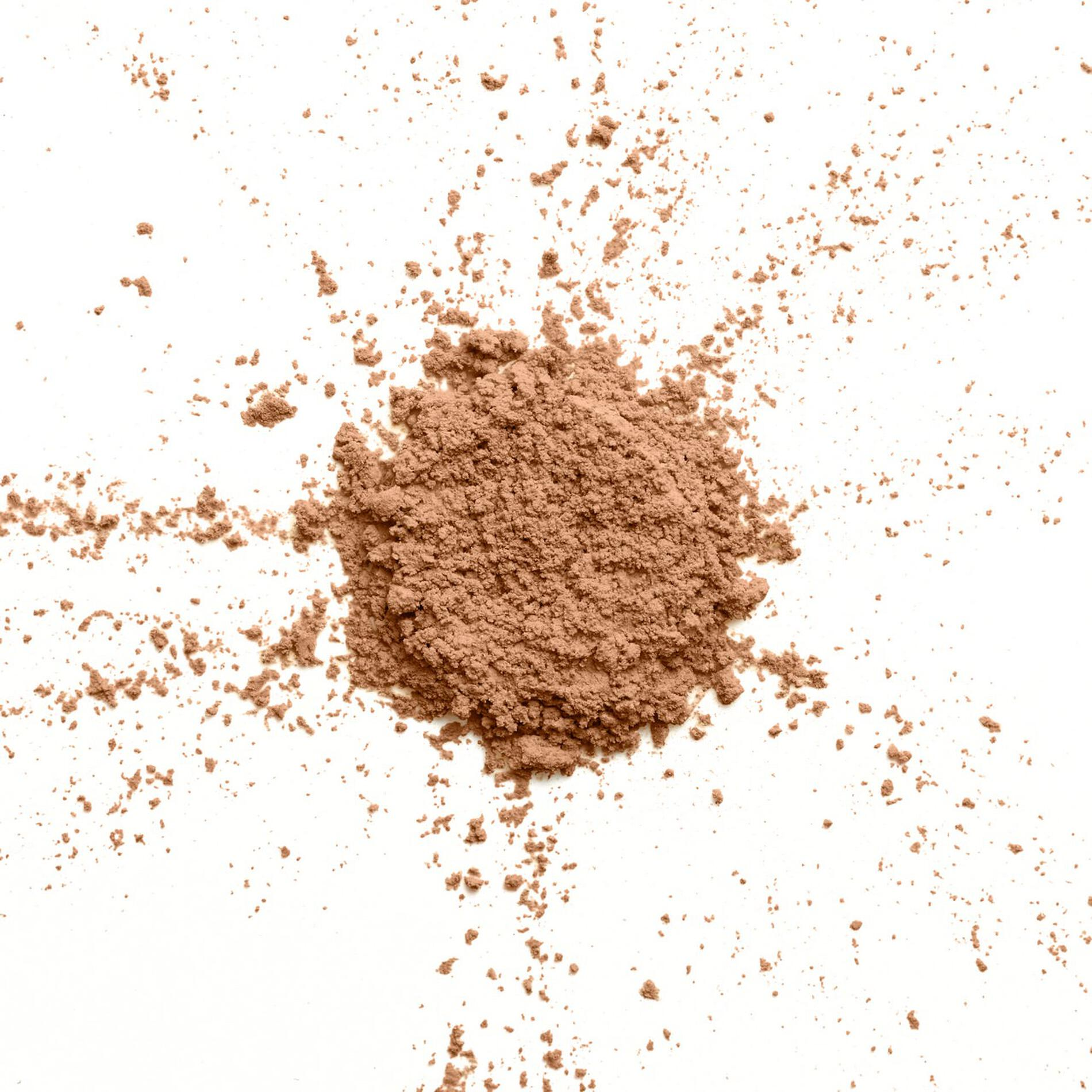 A pile of loose makeup setting powder with bits shooting off the sides as if it was dropped in place