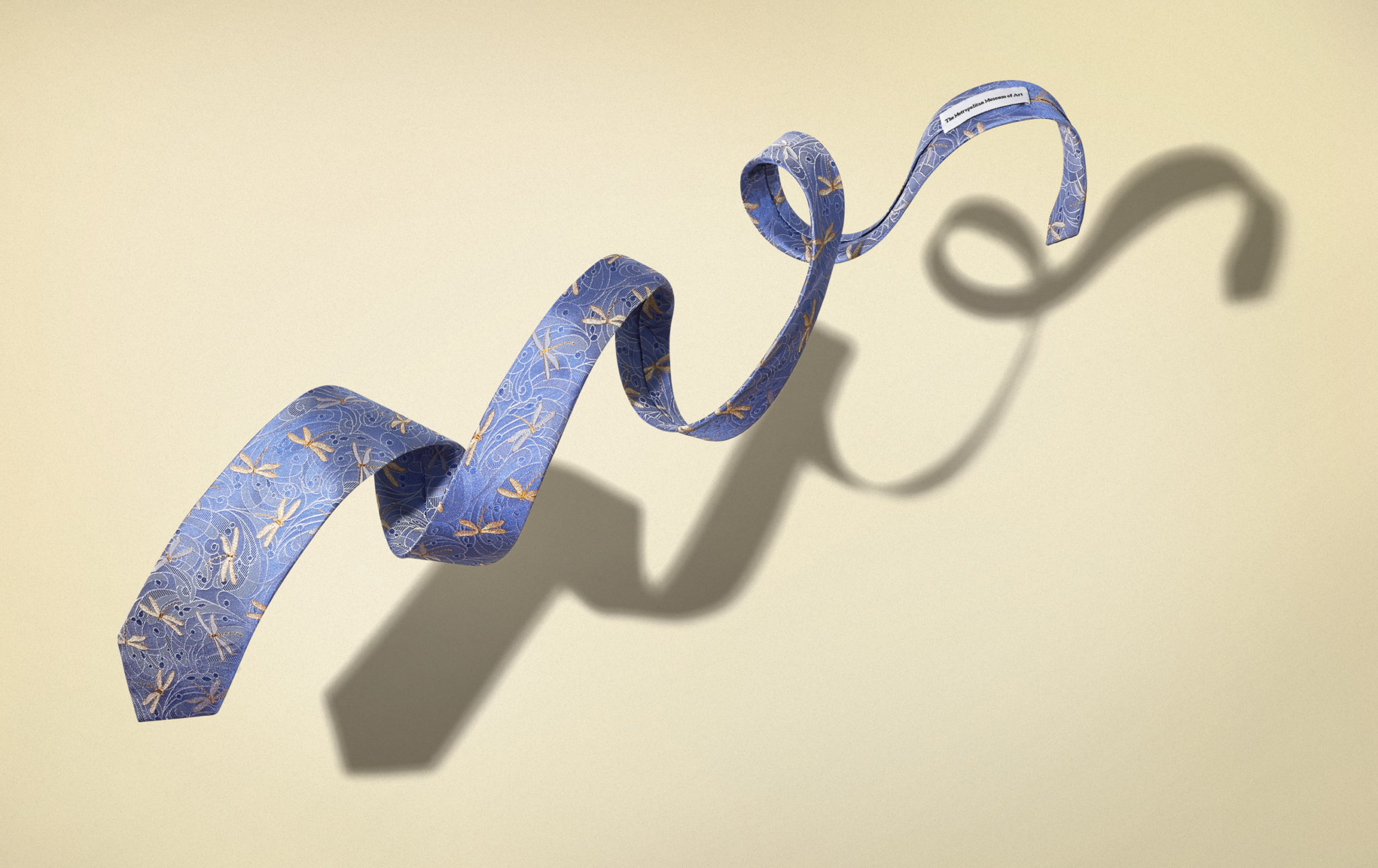 marketing photograph of a blue dragonfly print necktie floating or flying in front of a tan background.