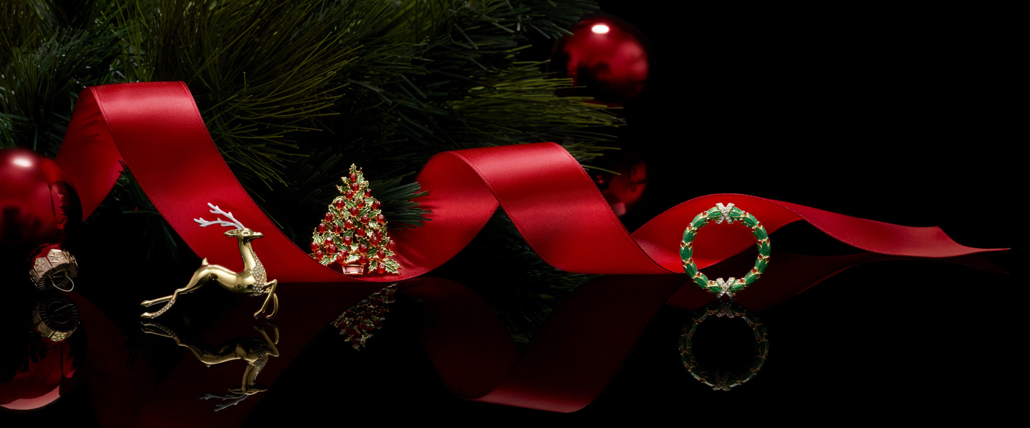 Holiday pins e-commerce header with a red ribbon, tree branch, reflection, and black background