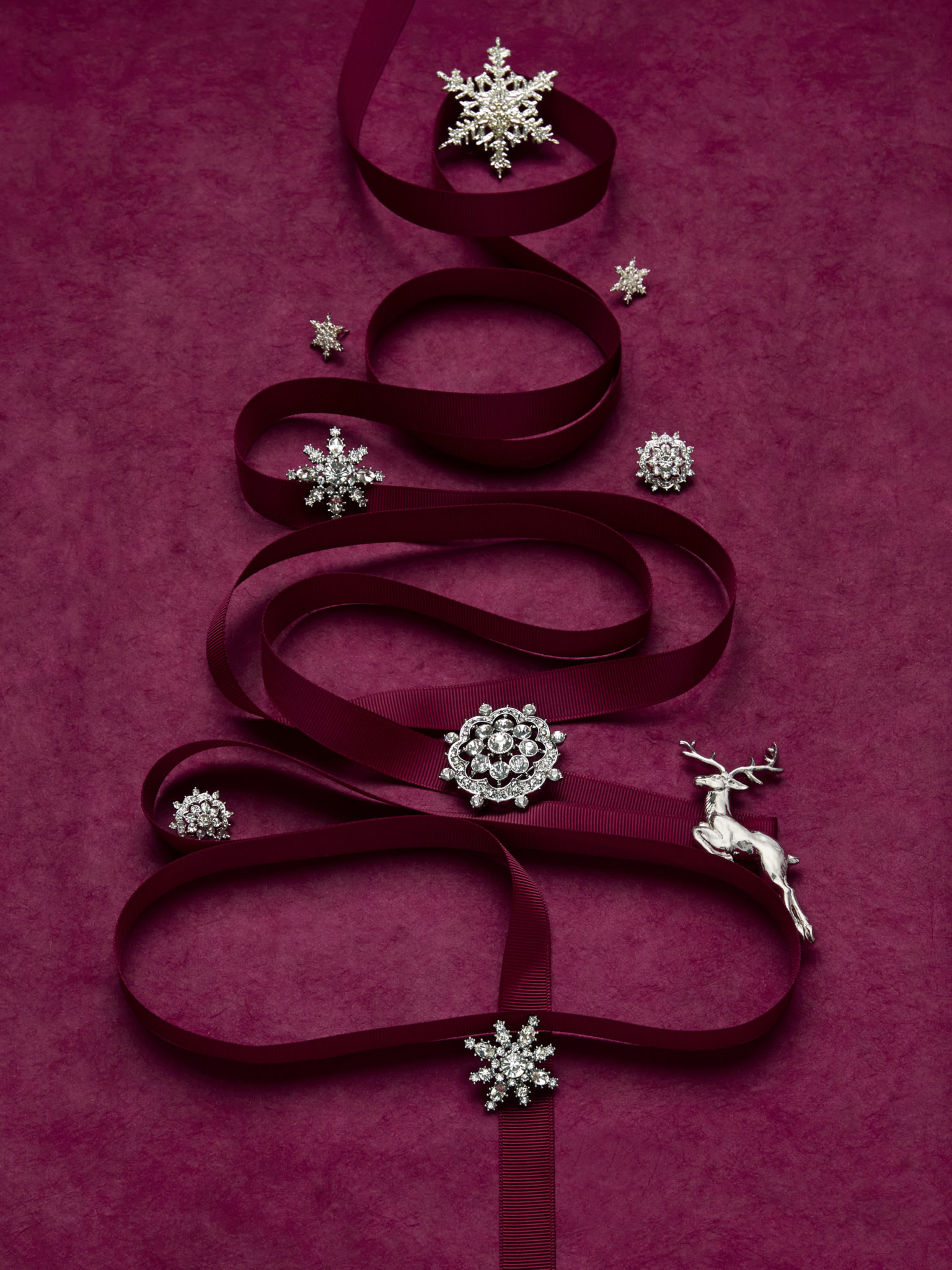 marketing still life photograph of silver and diamond jewelry including pins and earrings decorating a tree made of burgundy ribbon on a burgundy background