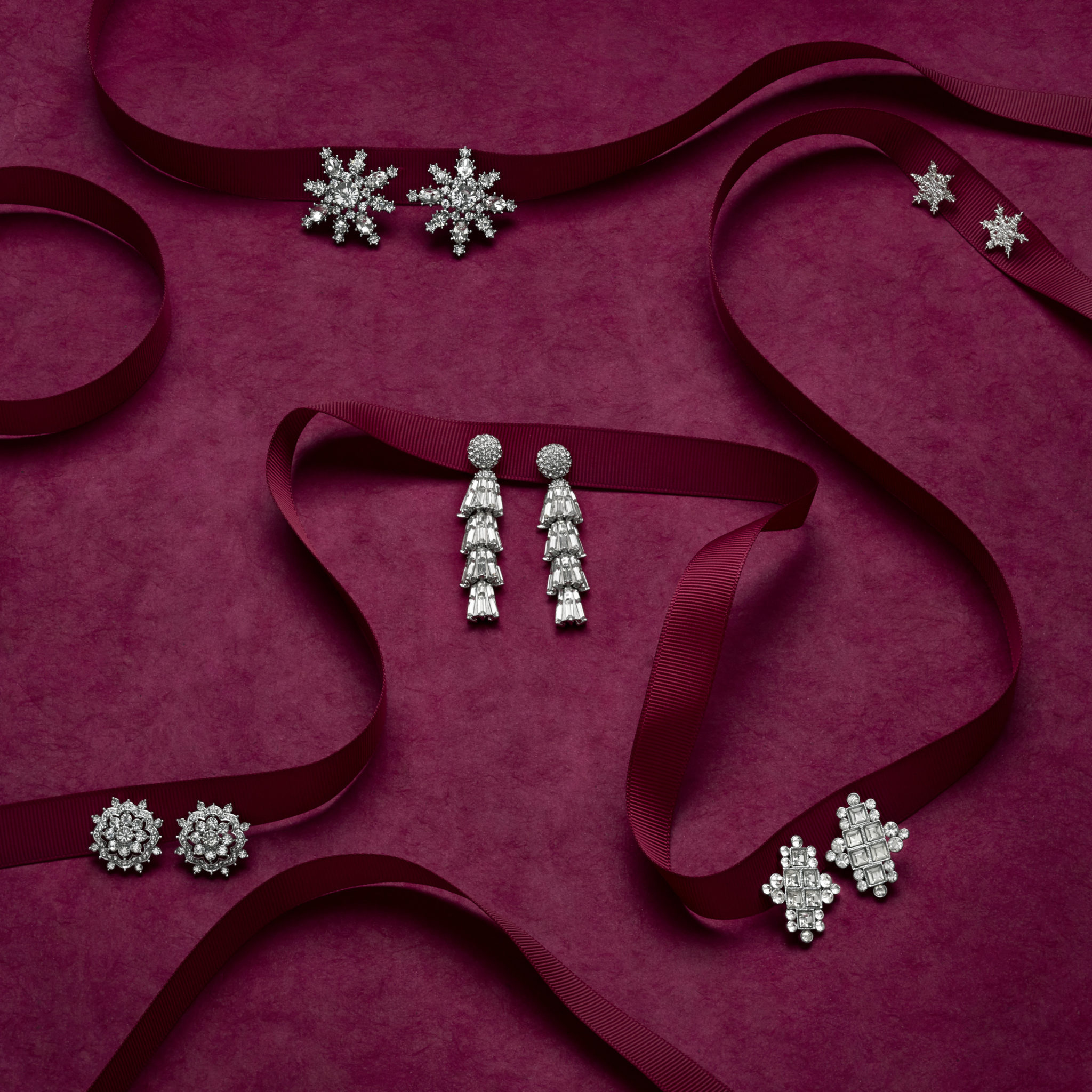 marketing still life photograph of silver and diamond earrings decorating burgundy ribbon on a burgundy background