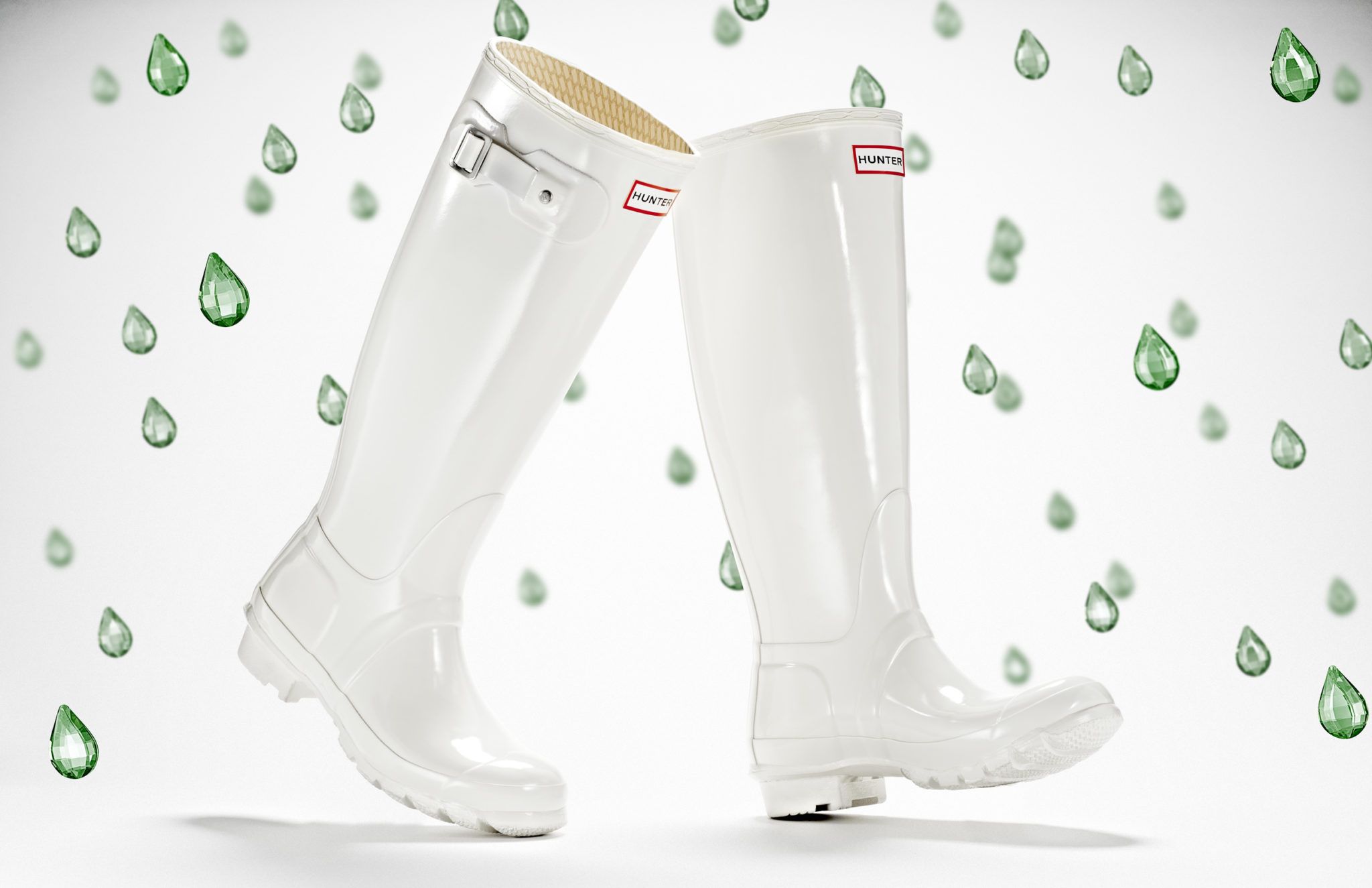 advertising still life photograph of white hunter boots surrounded by green jewel raindrops