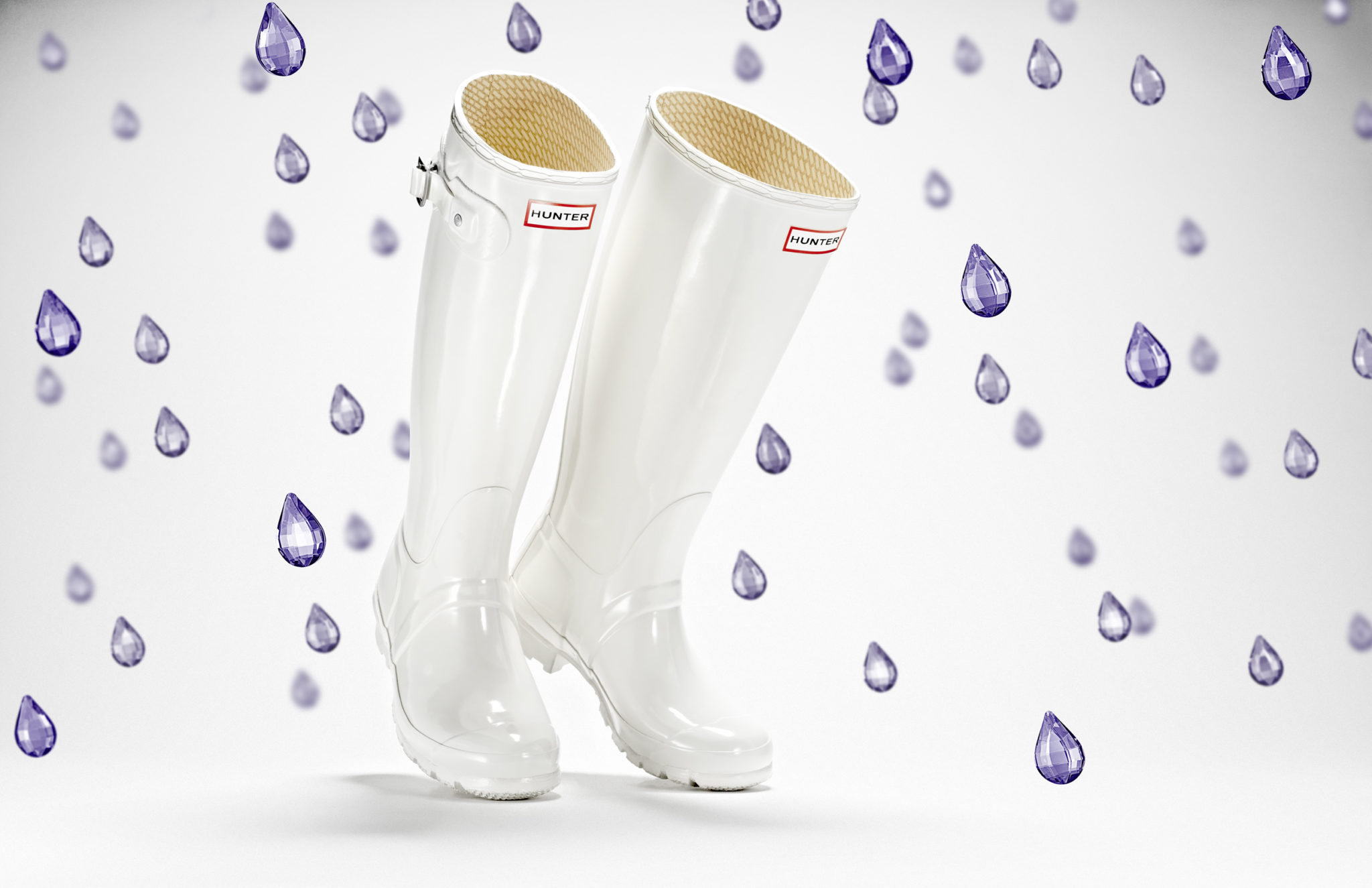 advertising still life photograph of white hunter boots surrounded by purple jewel raindrops