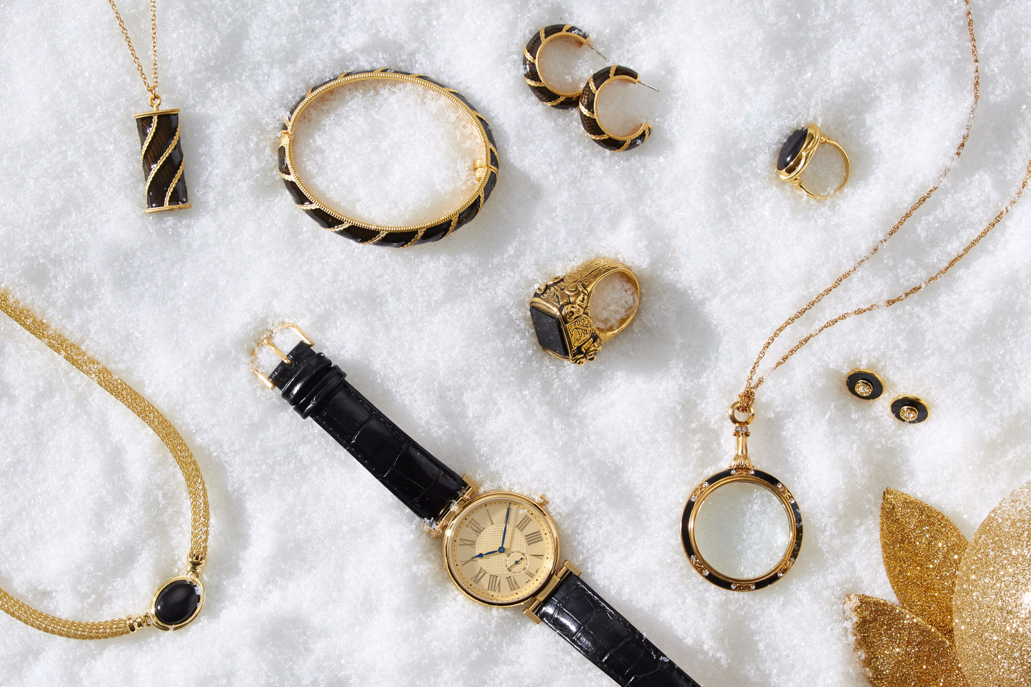 marketing still life photograph of black, gold and onyx jewelry including necklaces, earrings, rings, a bracelet, and a watch on snow