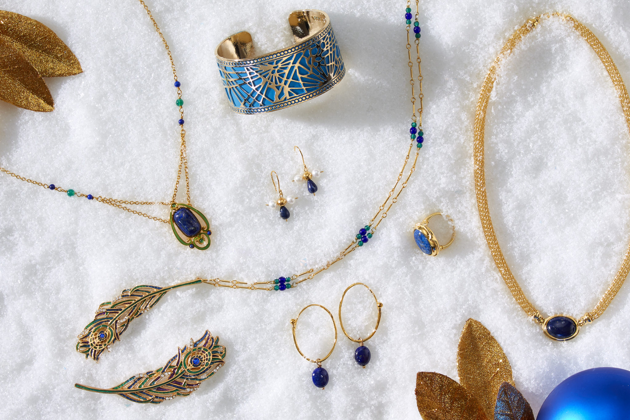 marketing still life photograph of blue, gold, and lapis jewelry including necklaces, earrings, a ring, a bracelet, and a pin on snow