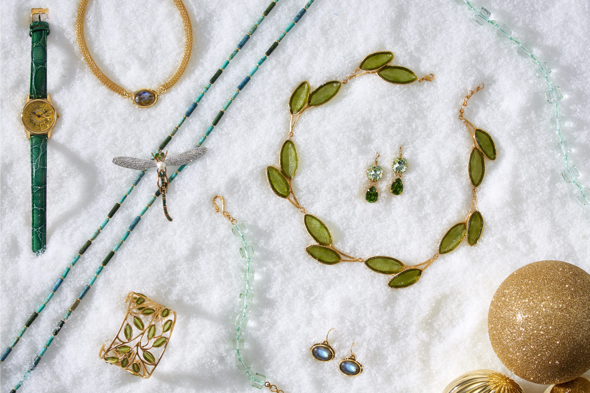 marketing still life photograph of green, gold, and turquoise jewelry including necklaces, earrings, bracelets, a watch, and a pin on snow
