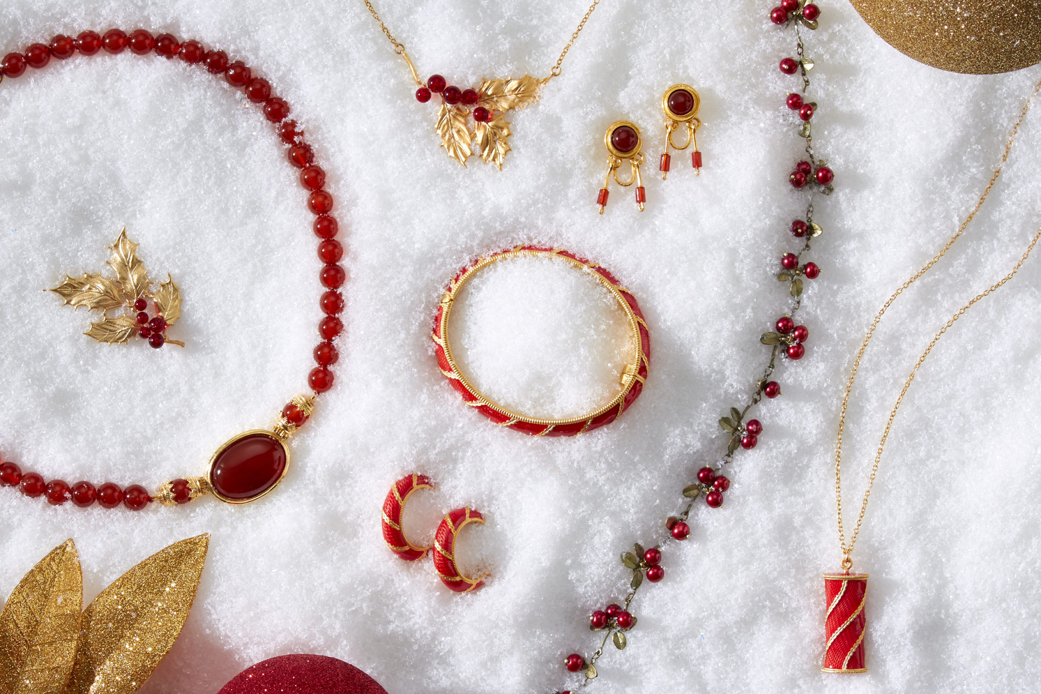 marketing still life photograph of red, gold, and garnet jewelry including necklaces, earrings, a bracelet, and a pin on snow