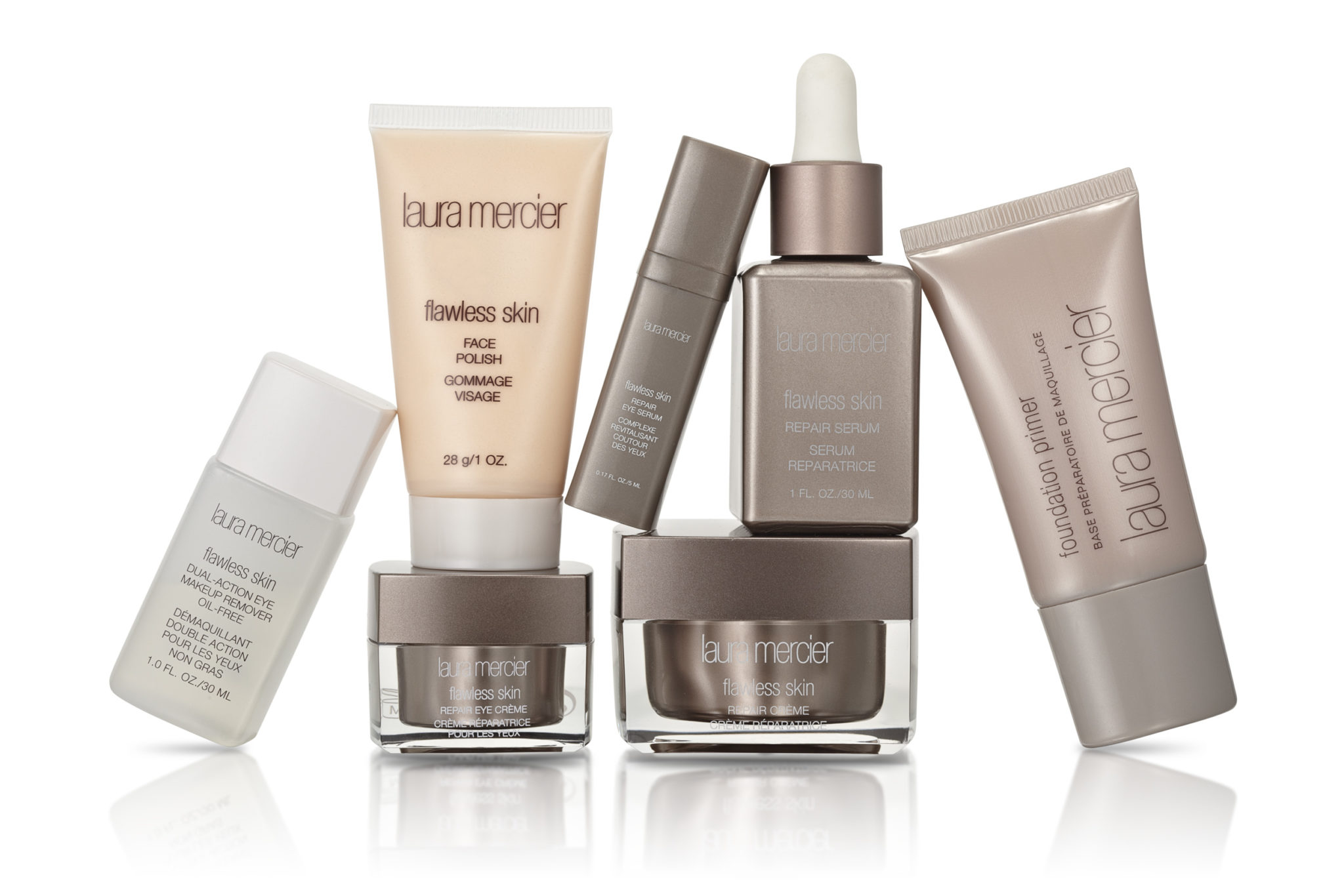e-commerce product photograph of seven skin care products including serums, cremes, and foundation in a dynamic group composition on white with a reflection