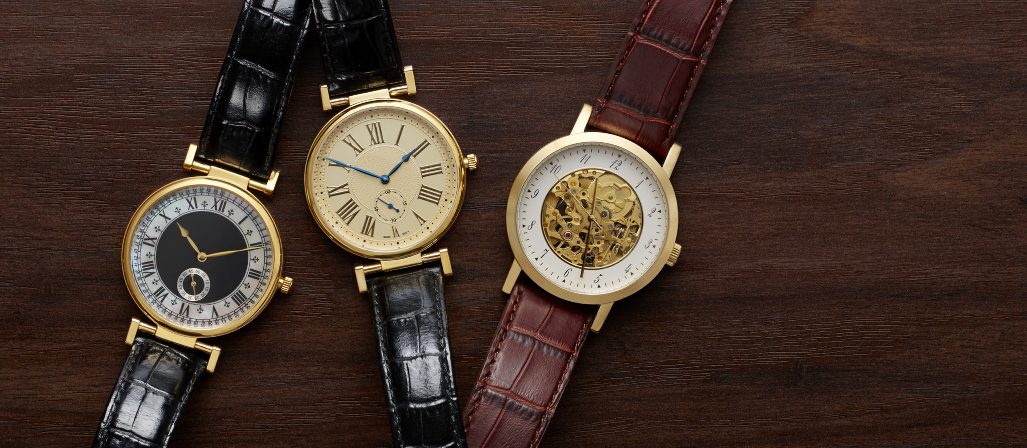 e-commerce header of three gold and leather mens watches on wood background