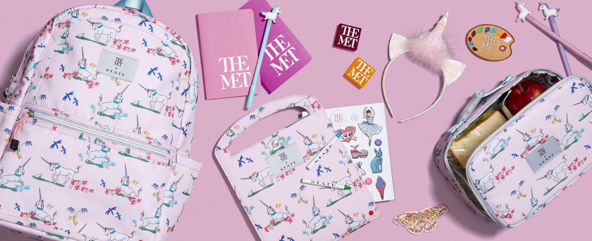 e-commerce header of the Met x State collaboration with unicorn backpack, lunch box, art folio, and supplies on pink background