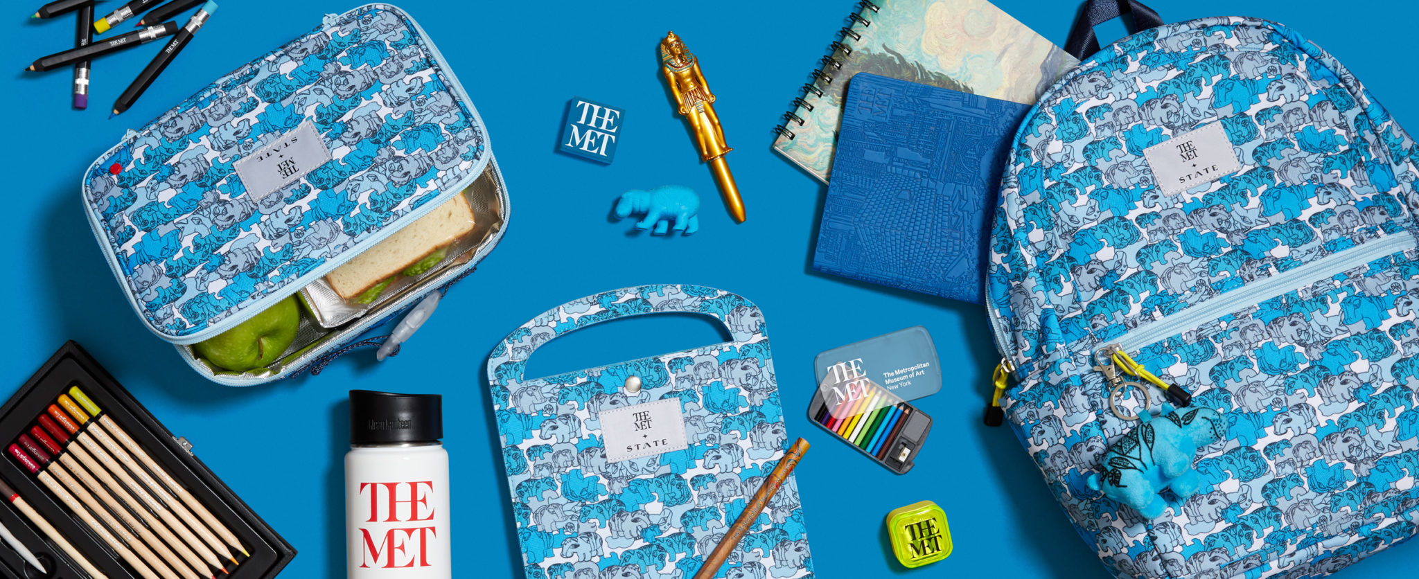 e-commerce header of the Met x State collaboration with hippo backpack, lunch box, art folio, and supplies on blue background