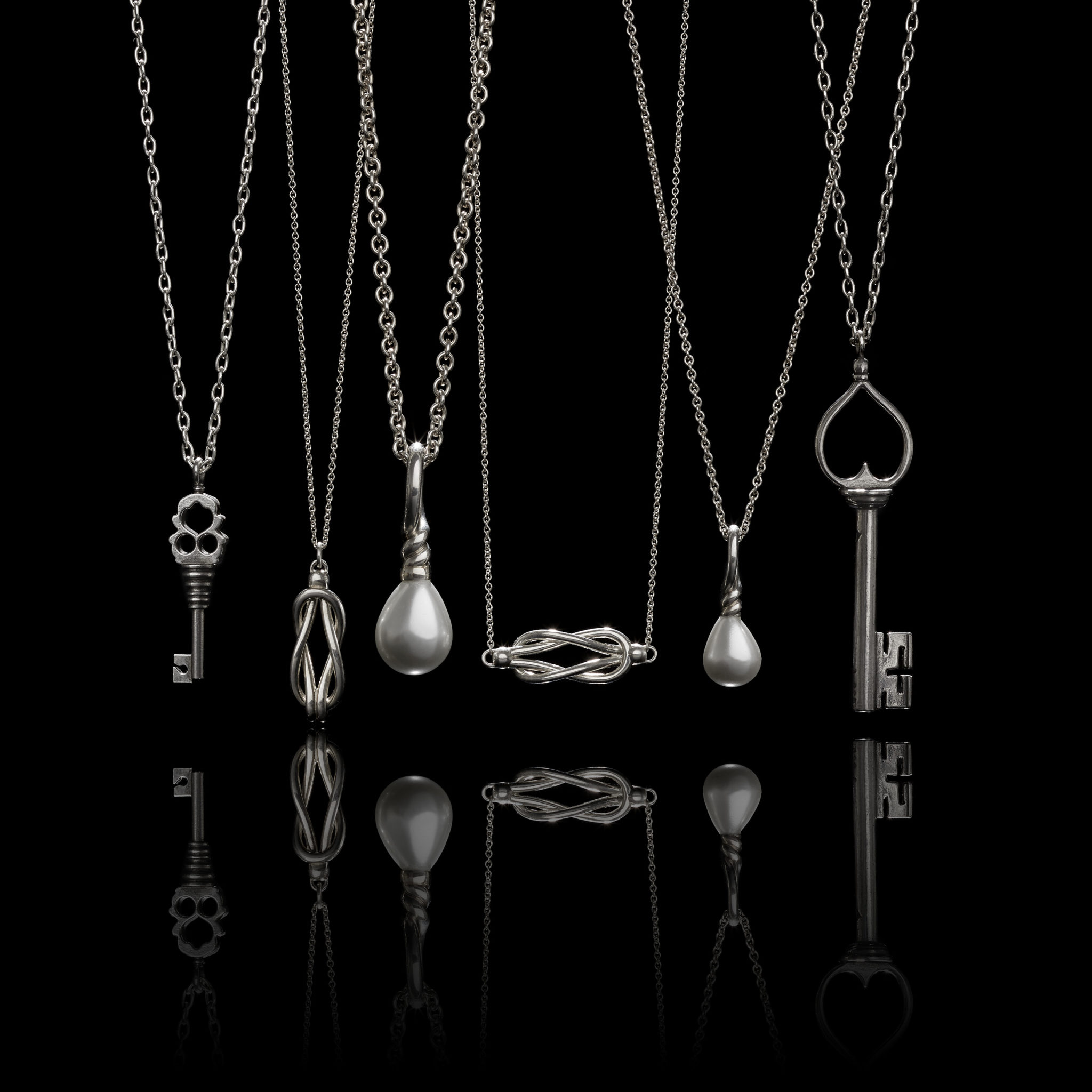 A group of silver pendant necklaces including keys, pearls, and knots with moody lighting, a reflection, and a black background