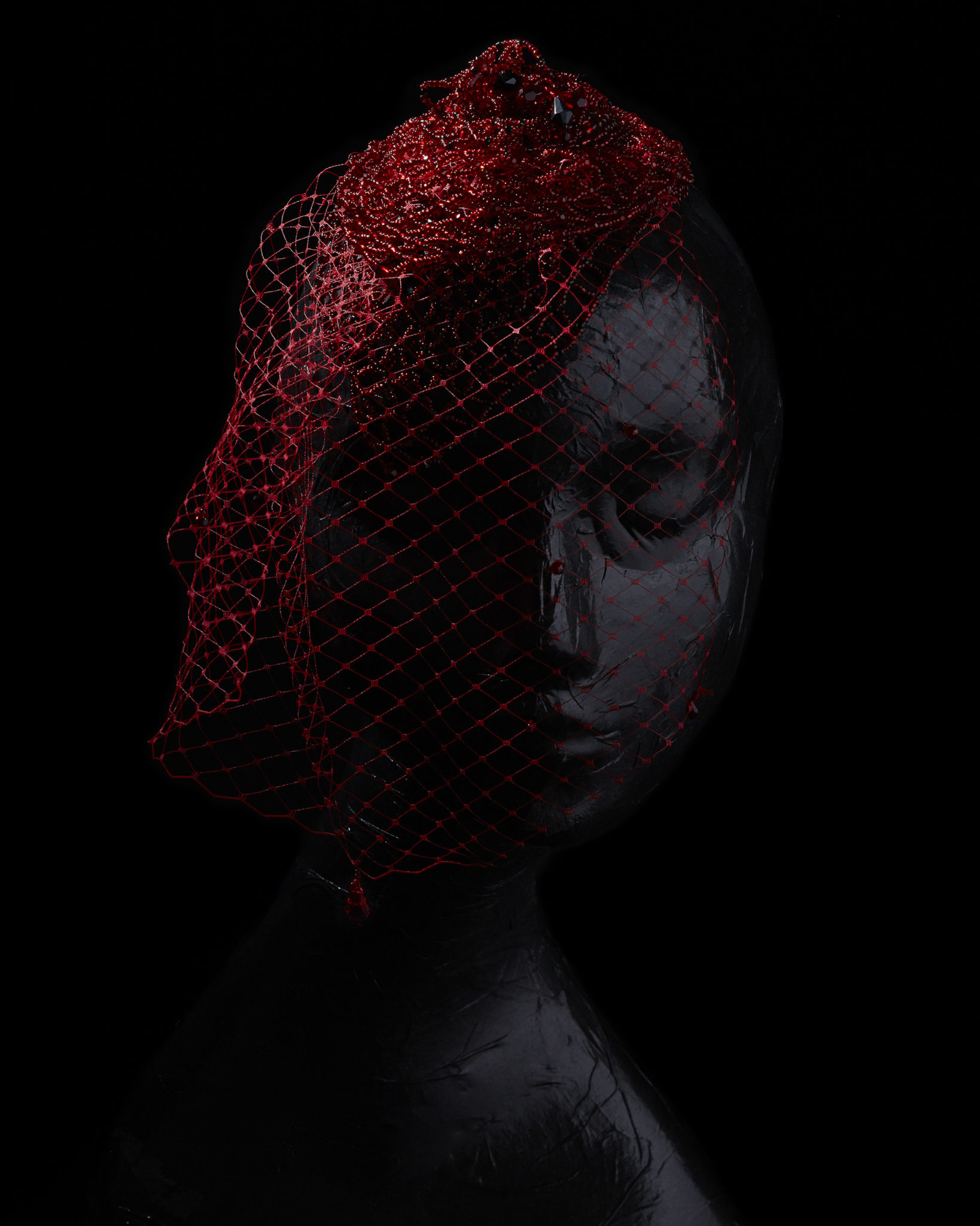 red beaded net hair piece and veil on a somber black mannequin on a black background