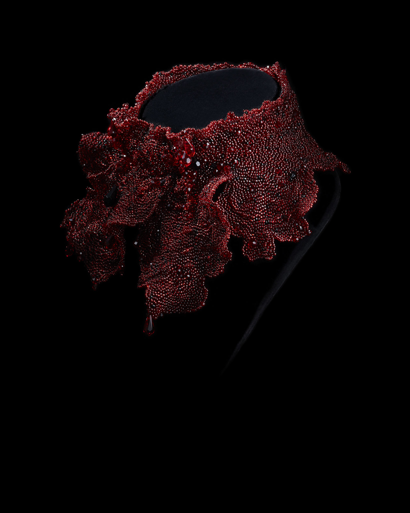 red beaded necklace on a black bust form on a black background