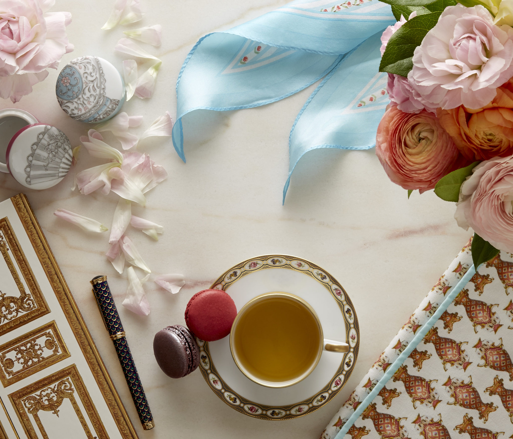 still life in warm window light of a journal and pen, a scarf, macrons, tea, a napkin, and flowers on marble